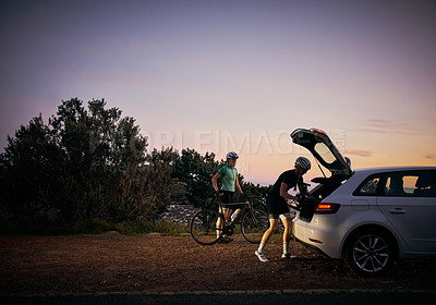 Buy stock photo Shot of two cyclist packing their bikes into the boot of their vehicle