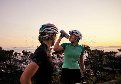 Buy stock photo Shot of two sporty young women taking a break while out cycling