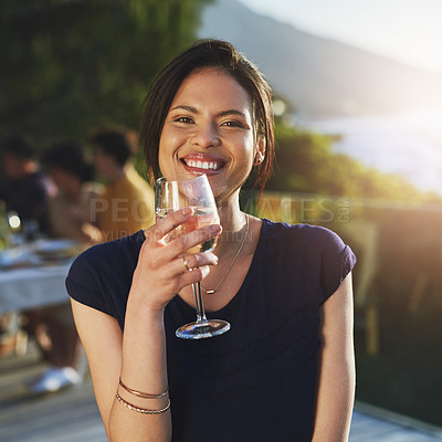 Buy stock photo Shot of an attractive young woman enjoying a glass of wine outdoors with her friends in the background