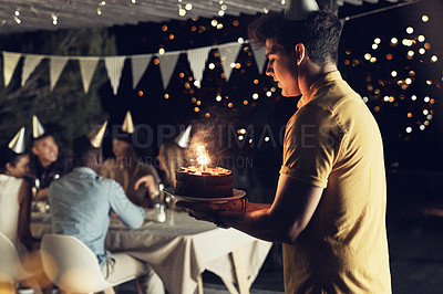 Buy stock photo Shot of a handsome young man carrying a cake at a birthday celebration with friends outdoors in the evening