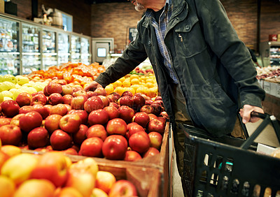 Buy stock photo Cropped shot of a man shopping for apples in a grocery store