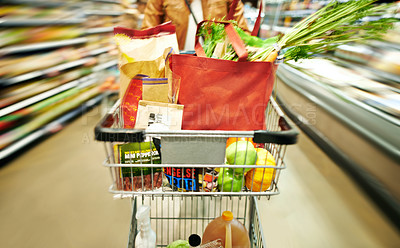 Buy stock photo Blurred shot of a woman pushing a trolley while shopping at a grocery store