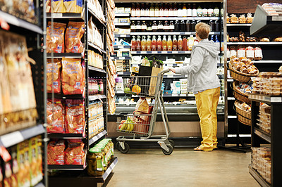 Buy stock photo Shot of a mature woman shopping in a grocery store