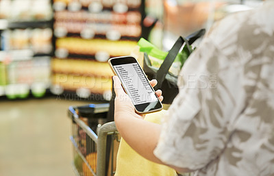 Buy stock photo Cropped shot of a woman using a mobile phone in a grocery store