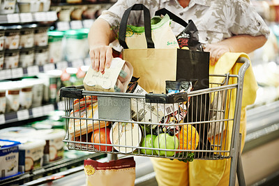 Buy stock photo Cropped shot of a woman shopping in a grocery store