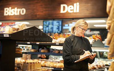 Buy stock photo Shot of a mature woman doing inventory in a grocery store
