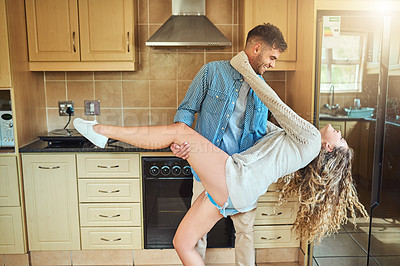 Buy stock photo Shot of a young couple dancing in the kitchen at home
