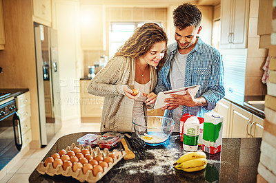 Buy stock photo Shot of a young couple mixing ingredients in their kitchen