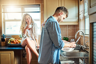 Buy stock photo Shot of a woman keeping her husband company while he does the dishes