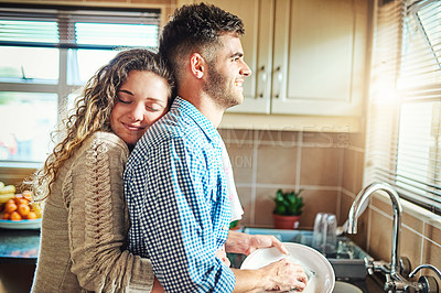 Buy stock photo Shot of a young woman embracing her boyfriend from behind while he does the dishes