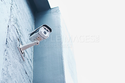 Buy stock photo Low angle shot of a security camera mounted on a wall outside a building