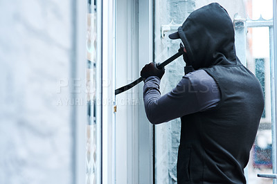 Buy stock photo Rearview shot of a male burglar using a steel weapon to break into a house