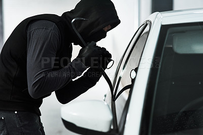 Buy stock photo Shot of a masked man using a steel weapon to break into a car inside a parking lot