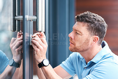 Buy stock photo Shot of a handsome mature locksmith installing a lock