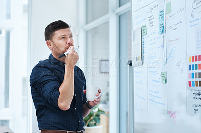 Buy stock photo Cropped shot of a handsome mature male designer working on a whiteboard in the office