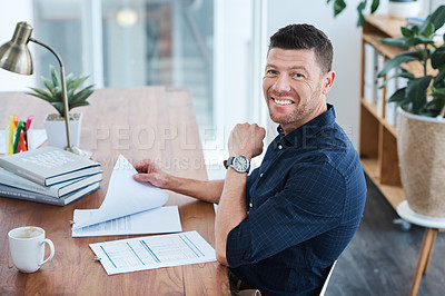 Buy stock photo Shot of a handsome mature businessman looking through some paperwork while sitting in his office