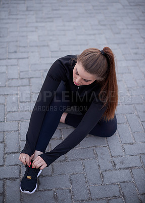 Buy stock photo High angle shot of an attractive young woman tying her laces before a run on the promenade