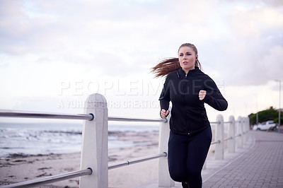 Buy stock photo Cropped shot of an attractive young woman out for a morning run on the promenade