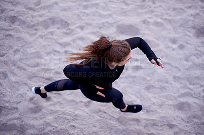 Buy stock photo High angle shot of an attractive young woman out for a morning run on the promenade