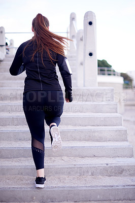 Buy stock photo Rearview shot of an unrecognizable young woman out for a morning run on the promenade