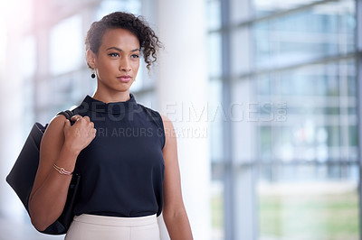 Buy stock photo Shot of a confident young businesswoman walking through a modern office
