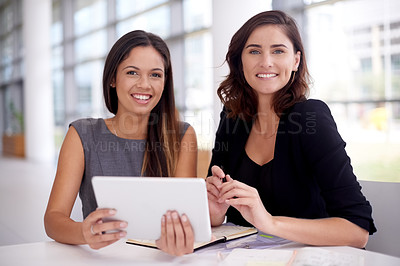 Buy stock photo Portrait of two young businesswomen using a digital tablet during a meeting in a modern office