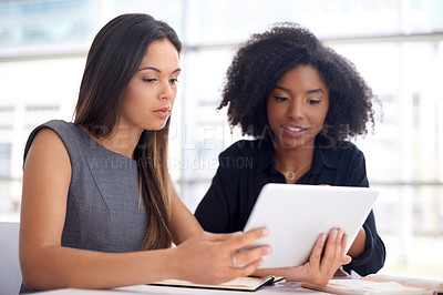Buy stock photo Shot of two young businesswomen using a digital tablet during a meeting in a modern office