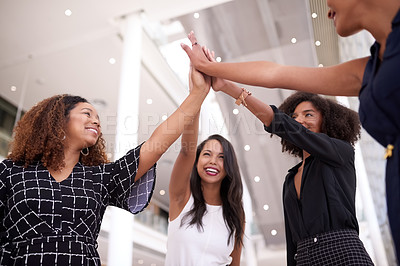 Buy stock photo Shot of a group of young businesswomen joining hands in a modern office