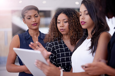 Buy stock photo Shot of a group of young businesswomen using a digital tablet in a modern office