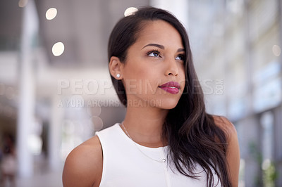 Buy stock photo Shot of a confident young businesswoman looking thoughtful in a modern office