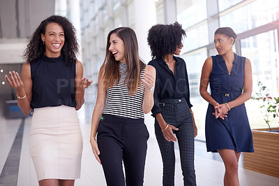 Buy stock photo Shot of a group of young businesswomen talking while walking through a modern office