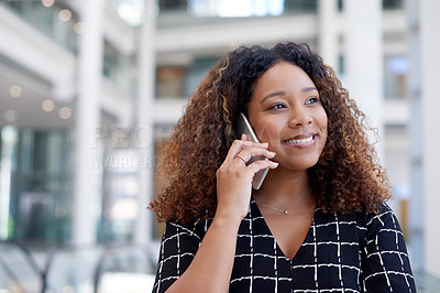 Buy stock photo Cropped shot of an attractive young businesswoman making a phonecall while standing in her office