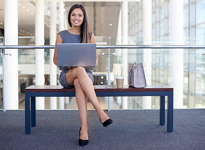 Buy stock photo Full length portrait of an attractive young businesswomen working on her laptop in the office
