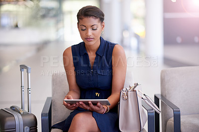 Buy stock photo Cropped shot of an attractive young businesswomen using her tablet while sitting in an airport departure lounge