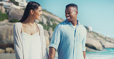 Buy stock photo Cropped shot of a happy young couple walking together along the seashore