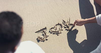 Buy stock photo High angle shot of an unrecognizable couple writing out their initials on sand at the beach