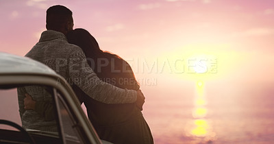 Buy stock photo Rearview shot of an affectionate young couple watching the sunset at the beach