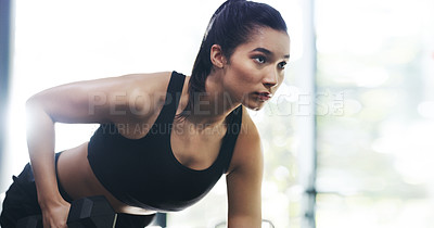 Buy stock photo Cropped shot of a focused young woman working out with dumbbells in a gym