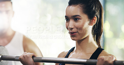 Buy stock photo Cropped shot of an attractive young sportswoman working out with a barbell in a gym