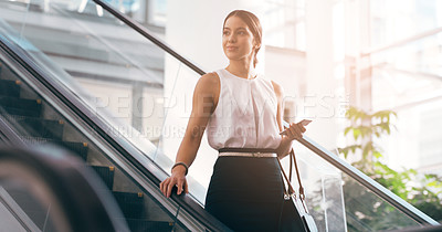 Buy stock photo Cropped shot of a young businesswoman on an escalator in the workplace