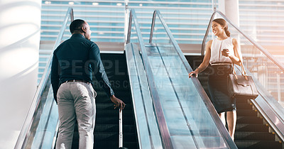 Buy stock photo Shot of two businesspeople talking while passing each other on escalators