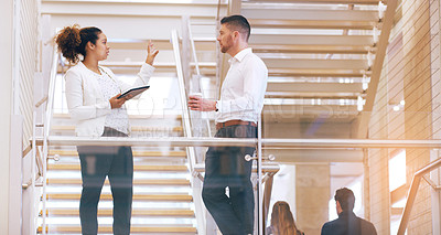Buy stock photo Cropped shot of two young businesspeople having a discussion while standing in a modern workplace