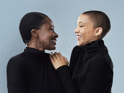 Buy stock photo Studio shot of two beautiful young women holding each other while standing against a grey background