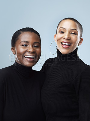 Buy stock photo Portrait of two beautiful young women holding each other while standing against a grey background