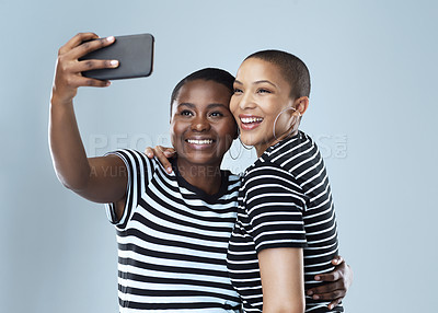 Buy stock photo Studio shot of two beautiful young women taking a selfie together against a grey background