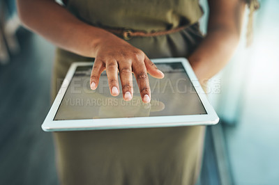Buy stock photo Cropped shot of an unrecognizable female designer using her tablet while standing in the office