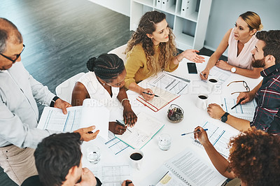 Buy stock photo High angle shot of a group of designers sitting in the boardroom during a meeting