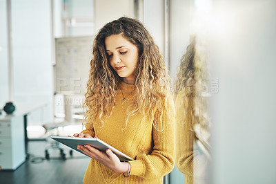 Buy stock photo Cropped shot of an attractive young female designer using her tablet while standing in the office