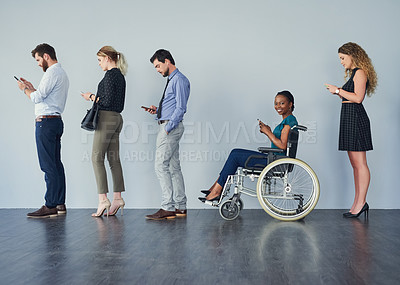Buy stock photo Portrait of a cheerful young woman seated in a wheelchair while texting on her phone and waiting in a line against a grey background