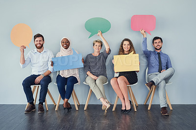 Buy stock photo Studio shot of a group of businesspeople holding colorful speech bubbles in line against a grey background